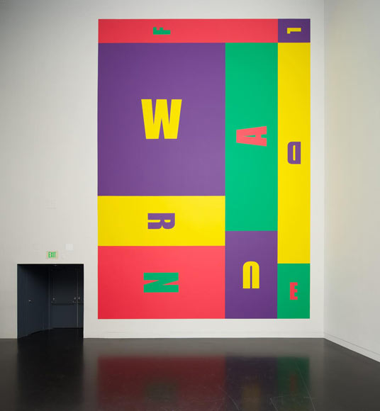 A photo of a wall painted with rectangles of color in purple, green, yellow and red. The letters of the word